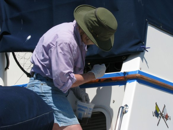 Alice varnishing the teak eyebrow trim on the flybridge