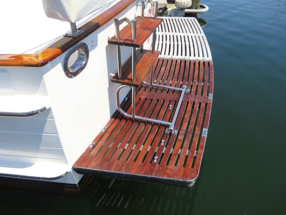 teak swim step half cleaned